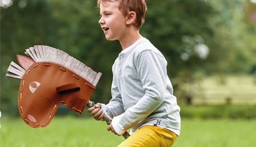 Kind mit gebasteltem Pferd